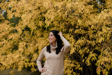 woman in tan sweater smiles standing against yellow trees