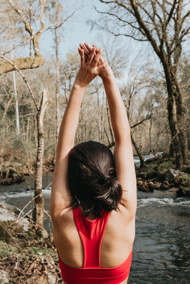 woman in vibrant red reaches arms up in a stretch outdoors