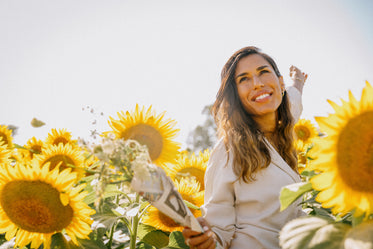 woman in white jacket smiles surrounded by sunflowers
