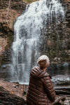 woman in winter fashion sits by foot of waterfall