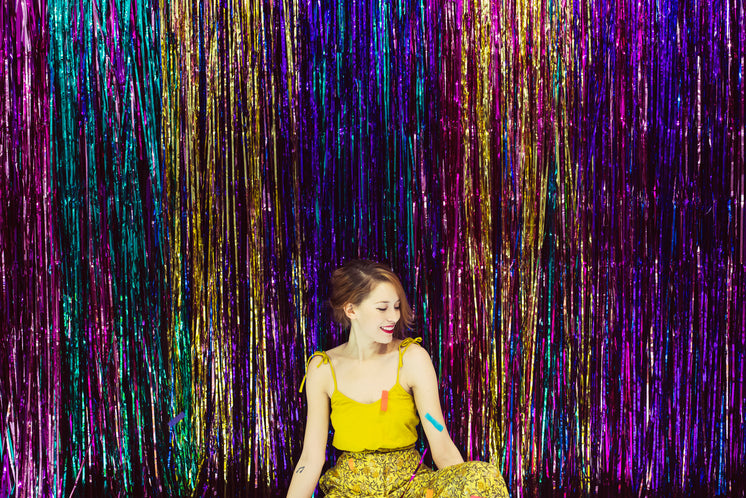 Woman In Yellow Smiles Against A Backdrop Of Streamers