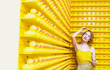 woman in yellow stands before a wall of rubber ducks