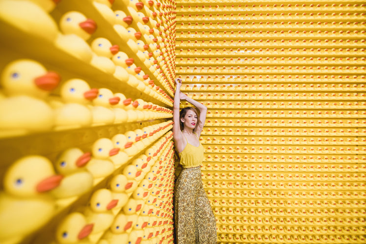 Woman In Yellow With Rows Of Rubber Ducks