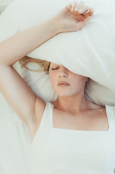 woman lays in a bed with a pillow over her head