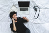 woman lays on her bed while talking on the cell phone