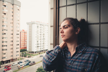woman leans on a tiled wall and looks out the window