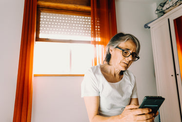 woman looks at her cell phone near a bright window