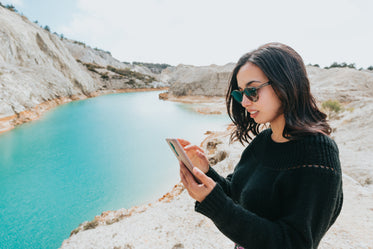 woman looks at her cellphone while by blue water