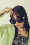 woman looks at the camera over bold black sunglasses