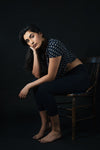woman looks forward while sitting on wooden chair