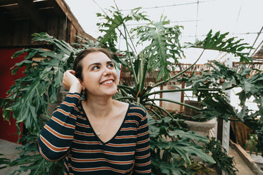 woman looks up and smiles by a large green plant