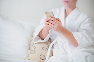 woman lounges in bathrobe with phone