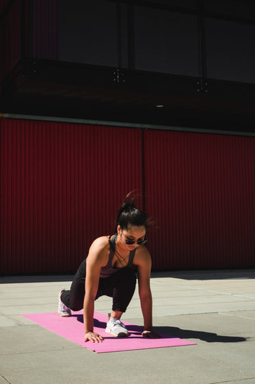 woman lunges forwards on a pink yoga mat