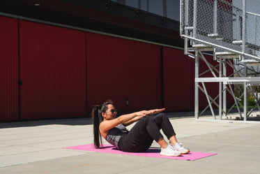 woman on a pink yoga mat crunches forward