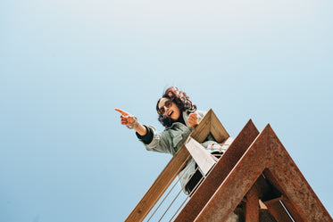 woman on a wooden deck points to something out of frame