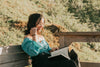 woman outdoors smiles while reading outdoors