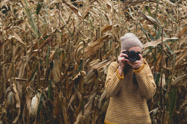 woman photographs field in fall