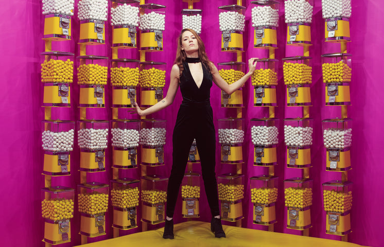 Woman Poses Against A Wall Of Gumball Machines