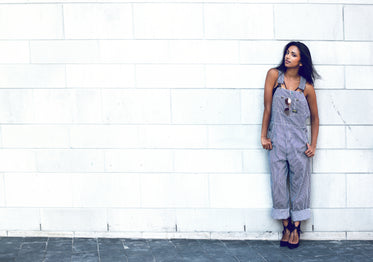 woman poses by brick wall in overalls