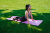 woman practices yoga in green grass