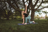 woman practices yoga under a large tree