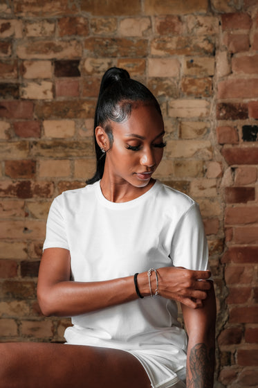 woman pulls on the sleeve of her blank white t shirt