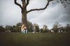 woman quietly reads a book under a tall tree