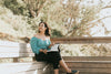 woman reads a book on a bench outdoors