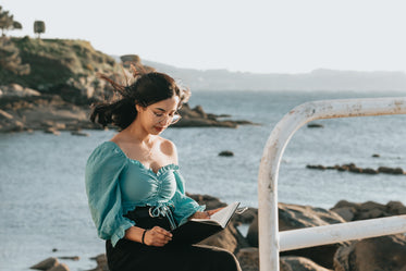 woman reads a book with rocks and water behind her