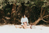 woman reads her book sitting on a wooden log on the beach