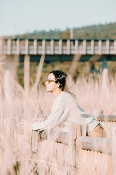 woman rests on a wooden fence outdoors