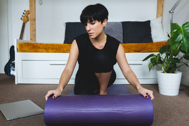 woman rolls purple yoga mat onto living room floor