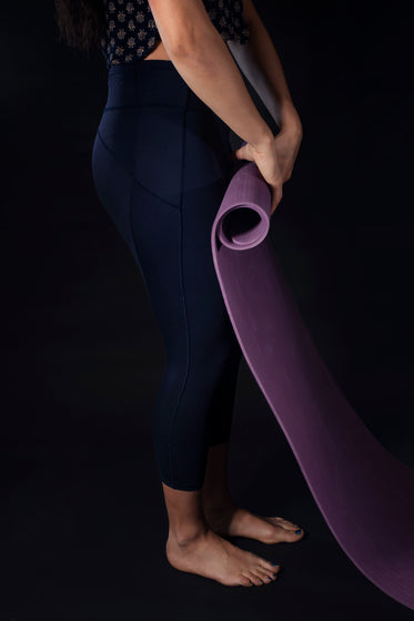 woman rolls up purple yoga mat