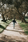 woman runs down a tree lined pathway