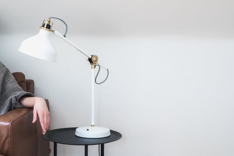 Woman's Hand On An Armrest Under A White Lamp