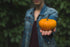 woman shows off small pumpkin