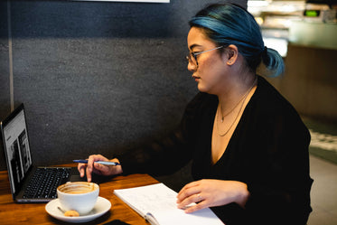 woman sits alone in a quiet cafe with a notebook and laptop