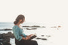 woman sits and reads a book by the rocky shore
