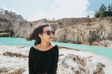 woman sits by rocks and aqua blue water