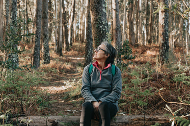 woman sits in a forest and looks up smiling