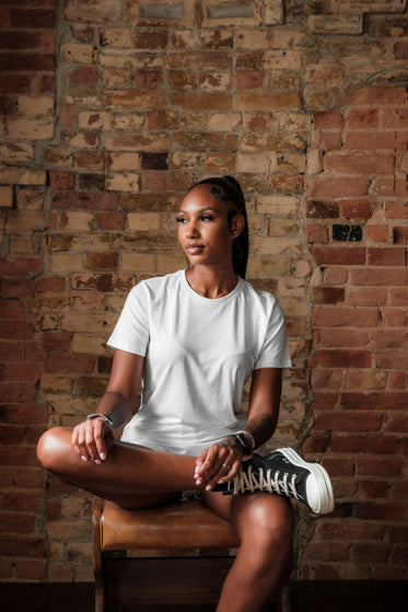 woman sits in front of a red brick wall in white t shirt