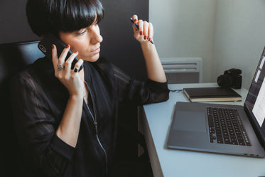 woman sits in front of computer talking on the phone