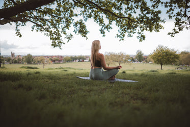 woman sits in self reflection under a tree