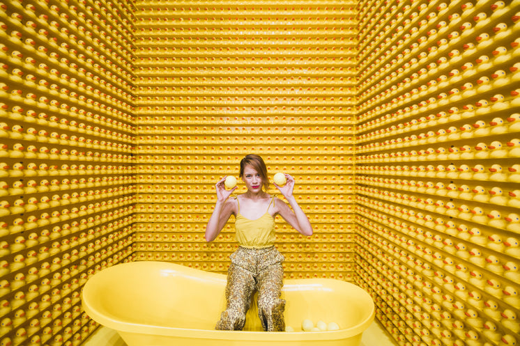 Woman Sits In Tub With Rubber Duckies