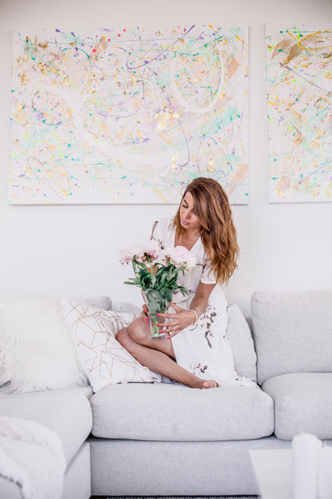 woman sits on a grey couch and holds a vase of peonies