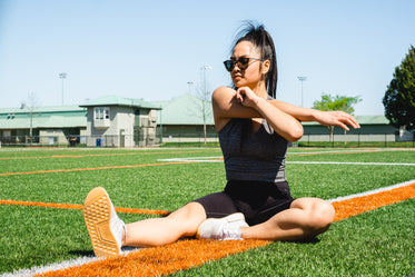 woman sits on a sports fields and stretches her arms