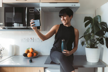 woman sits on her kitchen counter and takes selfie