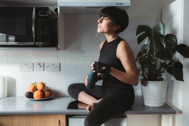 woman sits on kitchen counter in workout attire