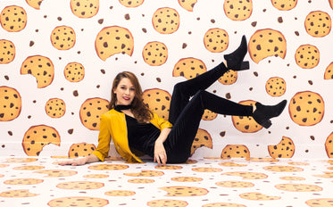 woman sits on the floor of a room covered cookie wallpaper