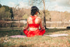 woman sits outdoors on a pink yoga mat